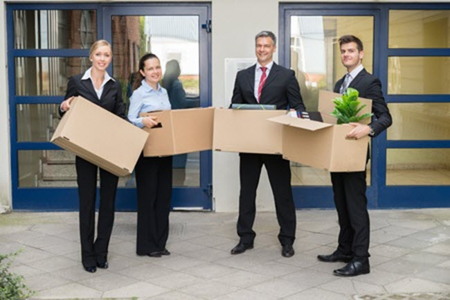 Office employees holding Sarasota commercial moving boxes