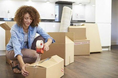 flat fee movers woman packing boxes
